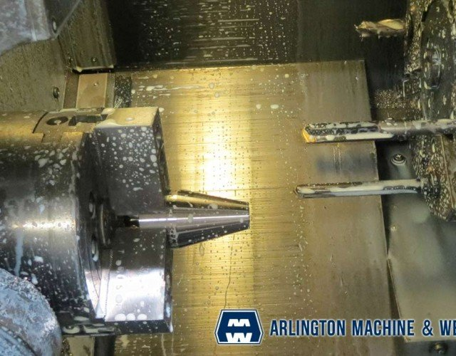Nozzle parts on lathe by Arlington Machine & Welding Inc.